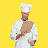Caucasian male chef in front of yellow background wearing uniform and holding paperwork
