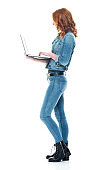 Caucasian female standing wearing boot and using computer