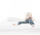 Caucasian female student in the bedroom wearing pajamas and holding book