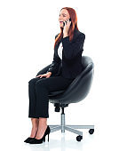 Caucasian female business person resting in front of white background wearing businesswear and using smart phone