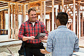 Young male owner repairing wearing plaid shirt and using digital tablet