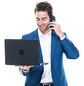 Caucasian young male businessman standing in front of white background wearing button down shirt and using computer