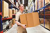 Caucasian young male manual worker at the warehouse wearing shirt and holding container