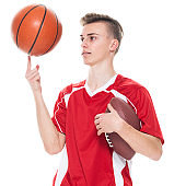 Caucasian young male american football player standing in front of white background wearing soccer uniform and holding basketball - ball and playing soccer - sport and using sports ball