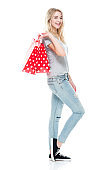 Generation z teenage girls shopaholic standing in front of white background wearing jeans and holding shopping bag