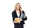 Caucasian female student standing and holding textbook