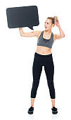 Generation z female exercising in front of white background wearing sports bra and holding placard