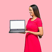 African-american ethnicity female standing in front of colored background wearing dress and using computer