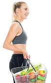Caucasian young women in front of white background wearing sports shoe and holding shopping basket