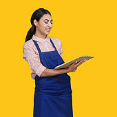 Latin american and hispanic ethnicity young women standing in front of yellow background wearing shirt and holding paperwork