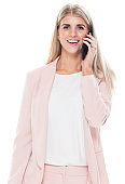 Caucasian young women businesswoman in front of white background wearing smart casual and holding purse and using smart phone