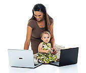 Mid adult women sitting on floor in front of white background and using laptop