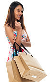 Female shopaholic standing in front of white background wearing dress and holding bag