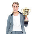 Caucasian female business person standing and holding trophy