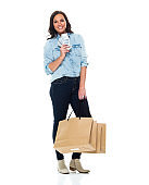 Caucasian female shopaholic in front of white background wearing jeans and holding currency