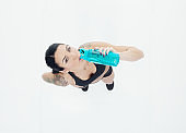 Caucasian female standing in front of white background wearing bra and holding water bottle