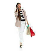Caucasian young women shopaholic walking in front of white background wearing coat - garment and holding bag