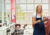 Caucasian young women owner standing at the nail salon wearing t-shirt and using mobile phone