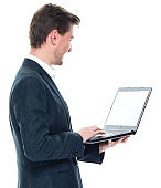 Caucasian young male businessman standing wearing businesswear and using computer
