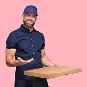 One person / waist up / front view of with with beard / brown hair / short hair caucasian male / young male pizza delivery person / delivery person standing in front of colored background who is delivering with home delivery