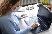 Woman wiping her laptop computer while working from home