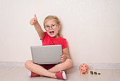 Happy little girl in eyeglasses using notebook laptop sitting on the floor at home with piggybank and coins money. Education homeschooling finance and savings concept. Smiling child showing thumb up gesture.