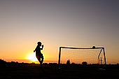 Boy Practicing Soccer Skills At Sunset