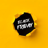 Black Friday text in paper hole teared in yellow paper over black background