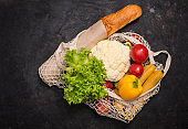 Eco friendly mesh bag with fruit and veggies on black background. No plastic. Zero waste and plastic free concept. Grocery shopping with eco bag. Sustainable and eco friendly lifestyle concept.