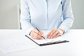 Woman's hands writing on sheet in a clipboard with a pen