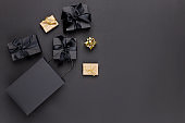 Black paper shopping bags and gift boxes on black background