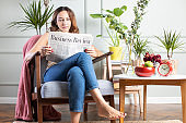 Young woman reading newspapers at home