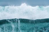 A dramatic close up of a crashing blue tubular wave