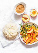 Ingredients for making peach mini pies - dough, fresh peaches, thyme, cane sugar on a light background, top view