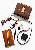 Women's cross body brown leather bag, business organizer, cosmetics and sunglasses on a light background, top view. Fashion beauty concept