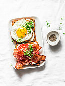 Delicious breakfast - sandwiches with cream cheese, fried egg, tomatoes, bacon on a light background, top view