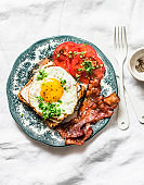 Nutritious breakfast - fried egg toast, bacon and tomatoes on a light background, top view