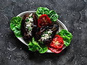 Greek style baked eggplant with feta cheese - delicious appetizer, tapas, snack on a dark background, top view