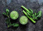 Vegetarian detox diet green smoothies with fresh celery, spinach, natural orange juice on a dark background, top view