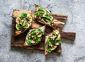 Bruschetta with grilled zucchini and cream cheese on a cutting board on a gray background, top view. Delicious tapas, appetizer