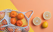 Fruits in cotton mesh bag on geometric background
