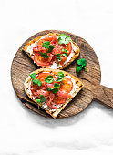 Smoked salmon, tomatoes, cream cheese, cilantro sandwich on a rustic cutting board on a light background, top view