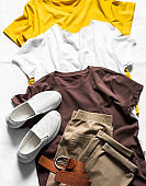 Women's clothing - three basic cotton t-shirts, sneakers and loose trousers slouchy on a light background, top view. Fashion concept