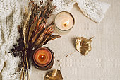 Background with warm sweaters, candles and dried flower bouquet. Cozy still life in warm shades, space for text.
