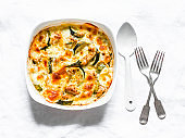 Zucchini, chicken, mozzarella cheese casserole on a light background, top view. Delicious lunch