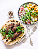Mediterranean style lunch table. Meat kebab, garlic herb naan, yogurt dressing vegetable salad, roasted potatoes - delicious lunch, tapas, snack in the  on a light background, top view
