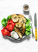 Vegetarian lunch, snack, tapas - rosemary roasted potatoes, grilled eggplant, tomatoes, green salad and greek cheese on a light background, top view