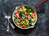 Vegetarian vegetable paella in a cooking pan on a dark background, top view