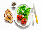 Delicious appetizers, tapas - stuffed roasted tomatoes, lettuce and grilled bread on a light background, top view