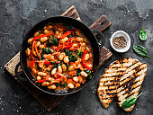Greek style tomato sauce, spinach, paprika, beans stew in a cast iron pan on a rustic board on a dark background, top view. Simple comfort food